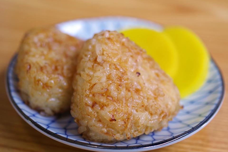 小皿ののったおにぎり二つとおいしそうな黄色いたくあん お昼ご飯
