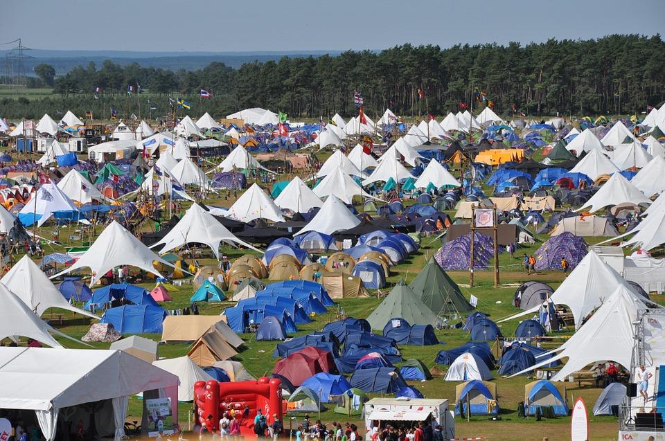 一面に張られた無数のテント 大勢の人がキャンプを楽しんでいる 青空と自然が美しい