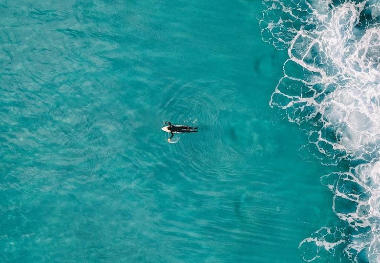 美しい大海原に一人で泳ぎ出す写真